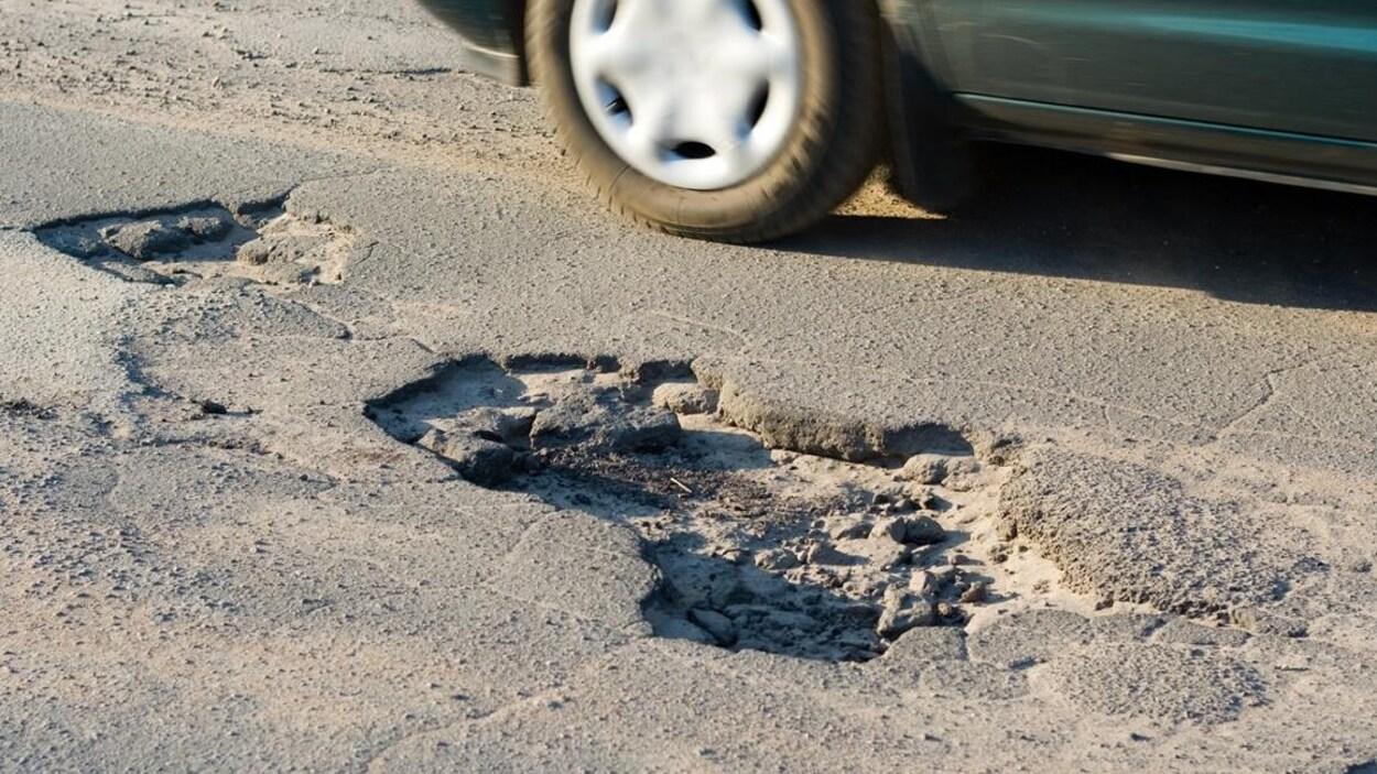 Une voiture évite un nid de poule.