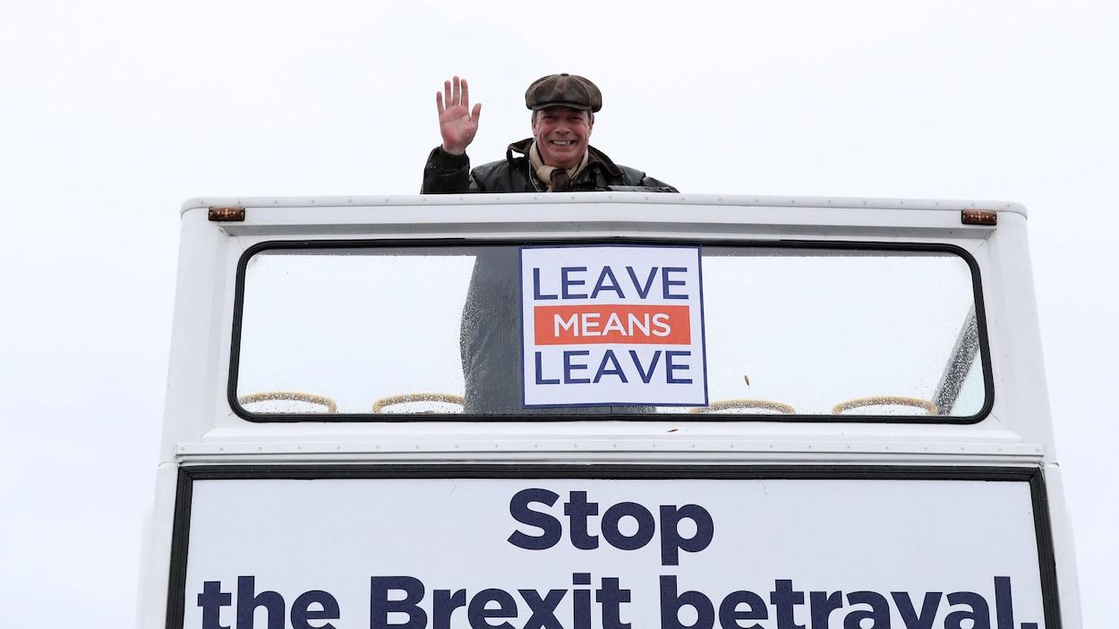 Nigel farage devant des pancartes sur lesquelles on peut lire «Partir veut dire partir» et «Arrêtons la trahison du Brexit».