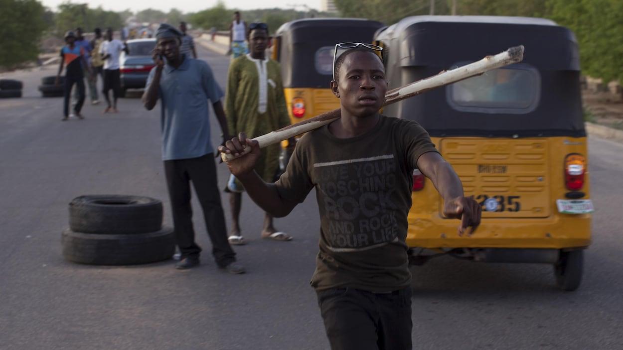 Des véhicules sont arrêtés par des jeunes. L'un d'eux tient un bâton.