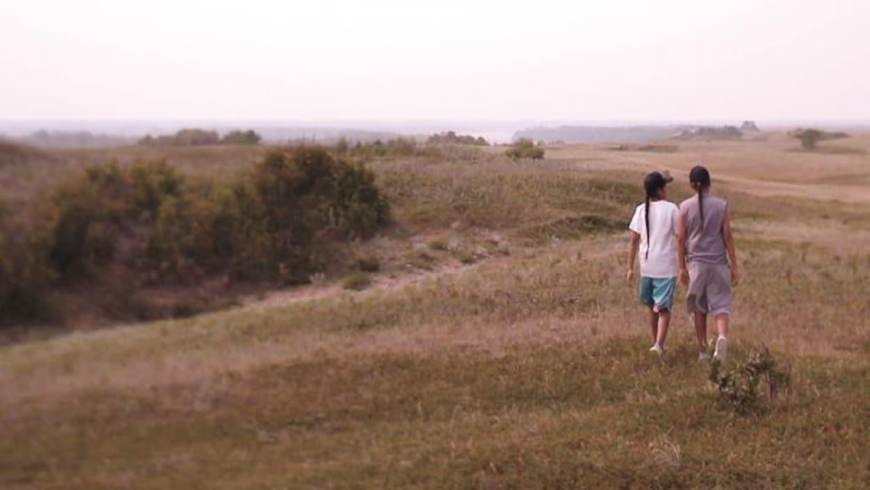 Deux Autochtones marchent dans un champ.