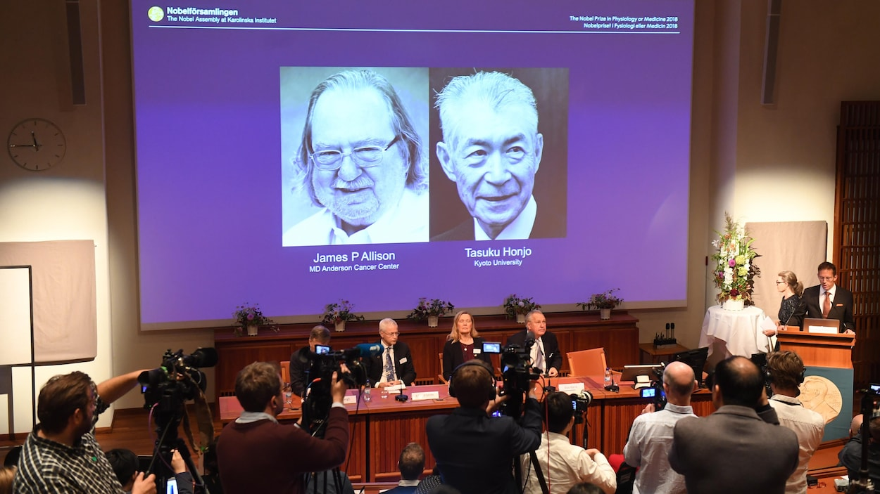 Les photos des lauréats du Nobel de médecine sont projetées sur un écran géant.