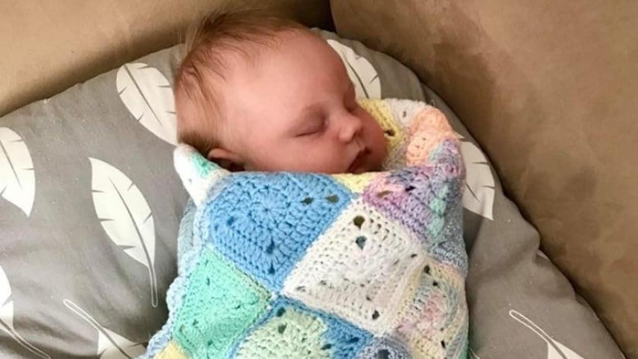 Le bébé de Carmen Bochek enveloppé dans la couverture en tricot multicolore.