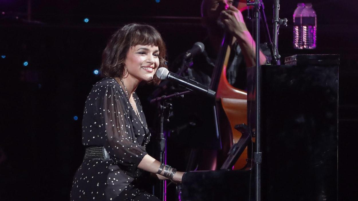 Assise au piano, Norah Jones sourit à la foule.
