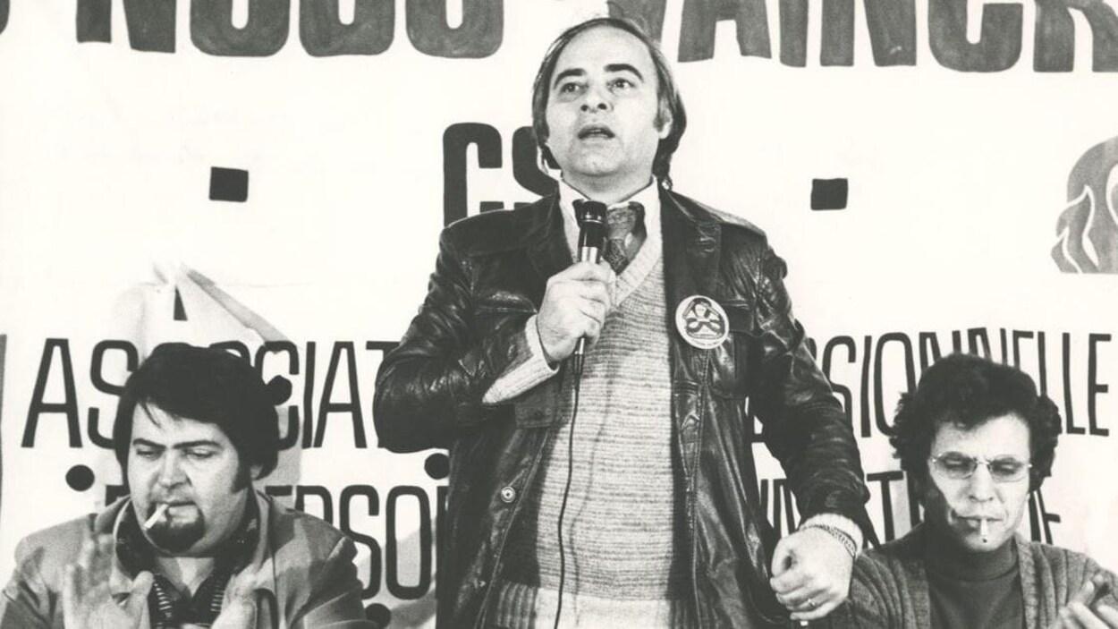 Un homme prend la parole un micro à la main. Il est entouré de deux autres hommes assis de chaque côté de lui.
