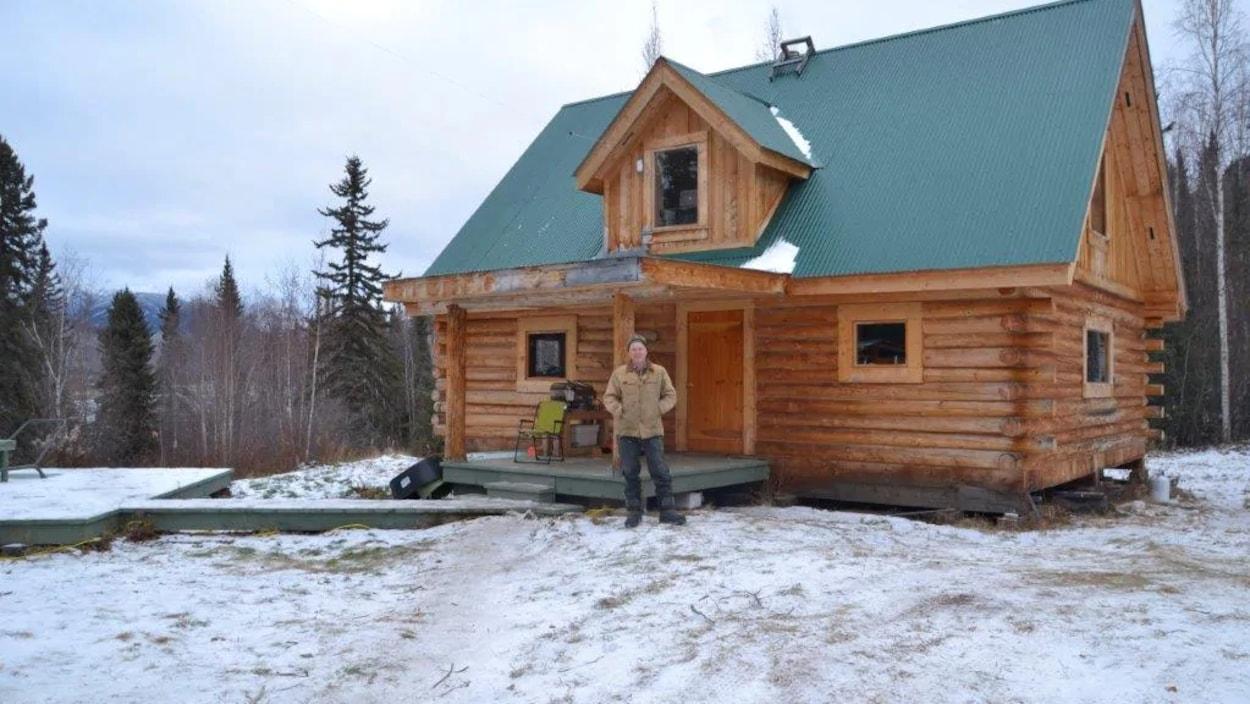 Norm Carlson est debout à l'extérieur devant sa maison en bois rond.