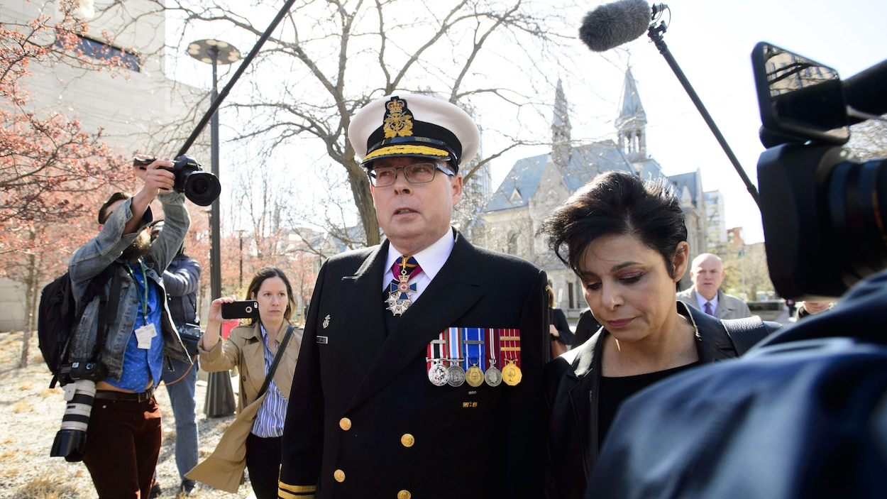 Mark Norman en tenue d'officier entouré de journalistes.