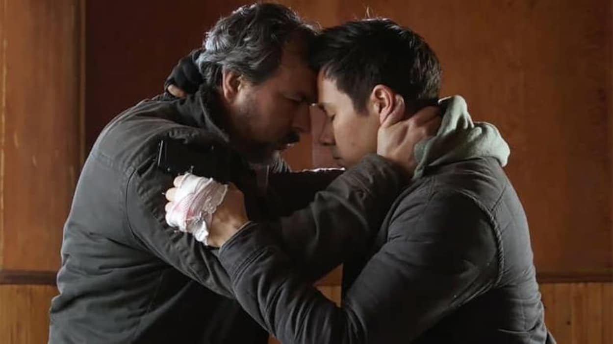 Deux hommes ont les yeux fermés et se tiennent enlacés l'un contre l'autre.