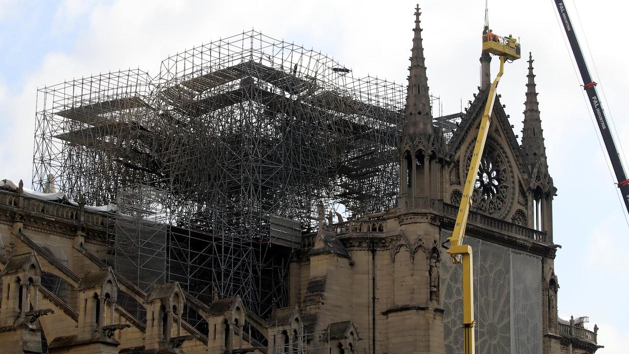 Des hommes travaillent à la restauration d'une statue située tout en haut de la cathédrale Notre-Dame de Paris.
