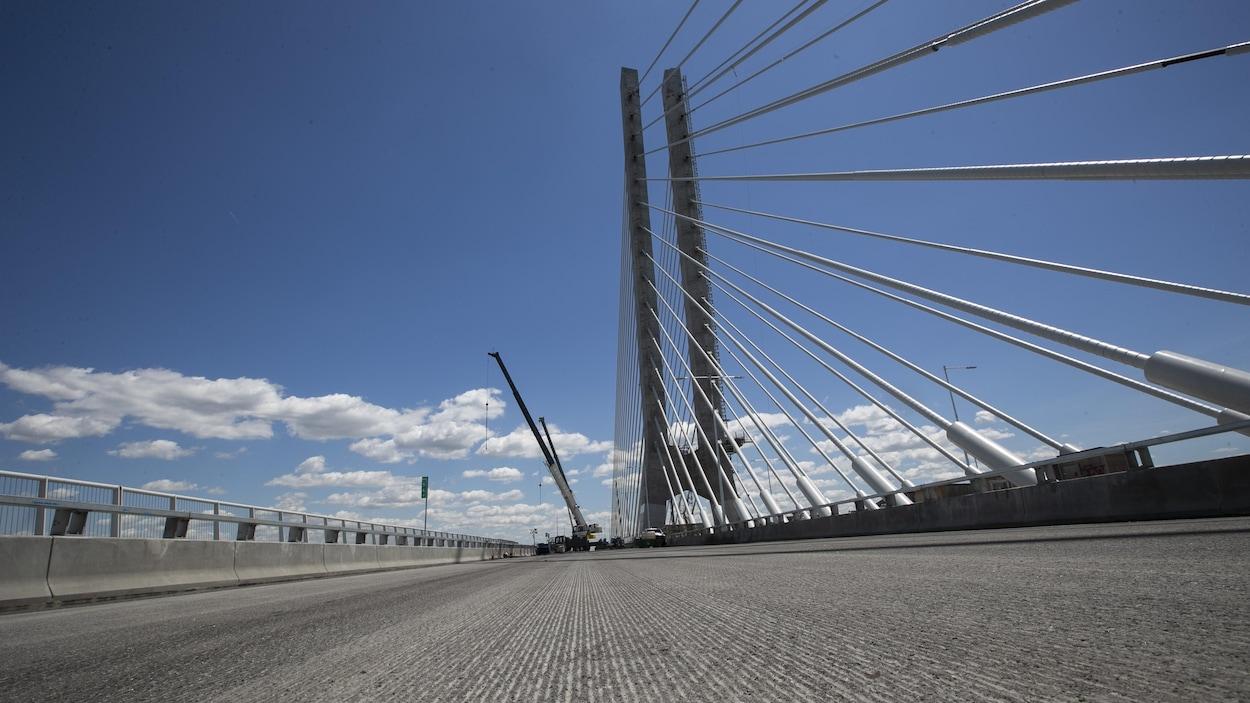 Des grues et du personnel s'activait encore sur le nouveau pont Samuel-De Champlain lorsque Radio-Canada a visité le chantier le 17 juin 2019.