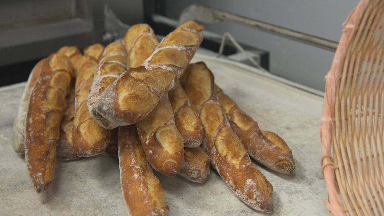 Des baguettes de pain empilées déposées sur une table.