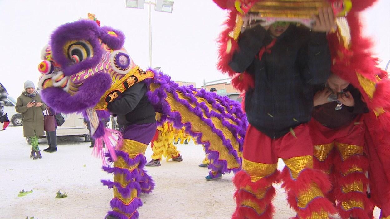 Des danseurs, vêtus de costumes de lion, imitent le gestuel des lions dans un stationnement.