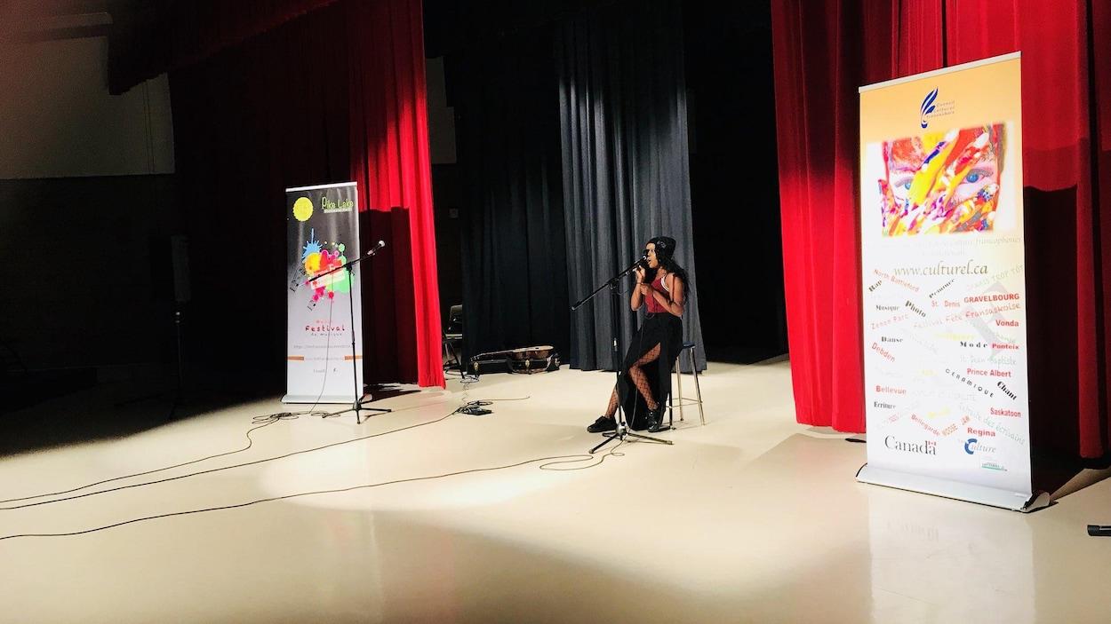 Une jeune femme qui chante assise sur un tabouret