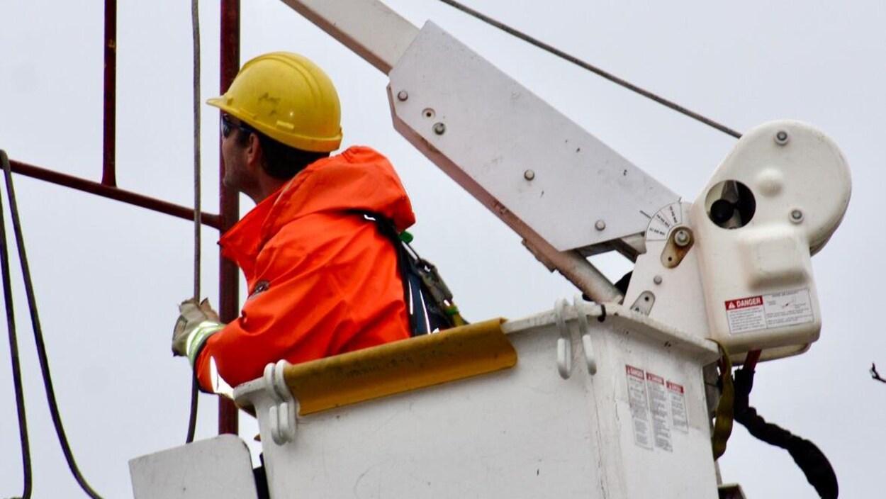 Un travailleur de la compagnie d'électricité dans une nacelle.