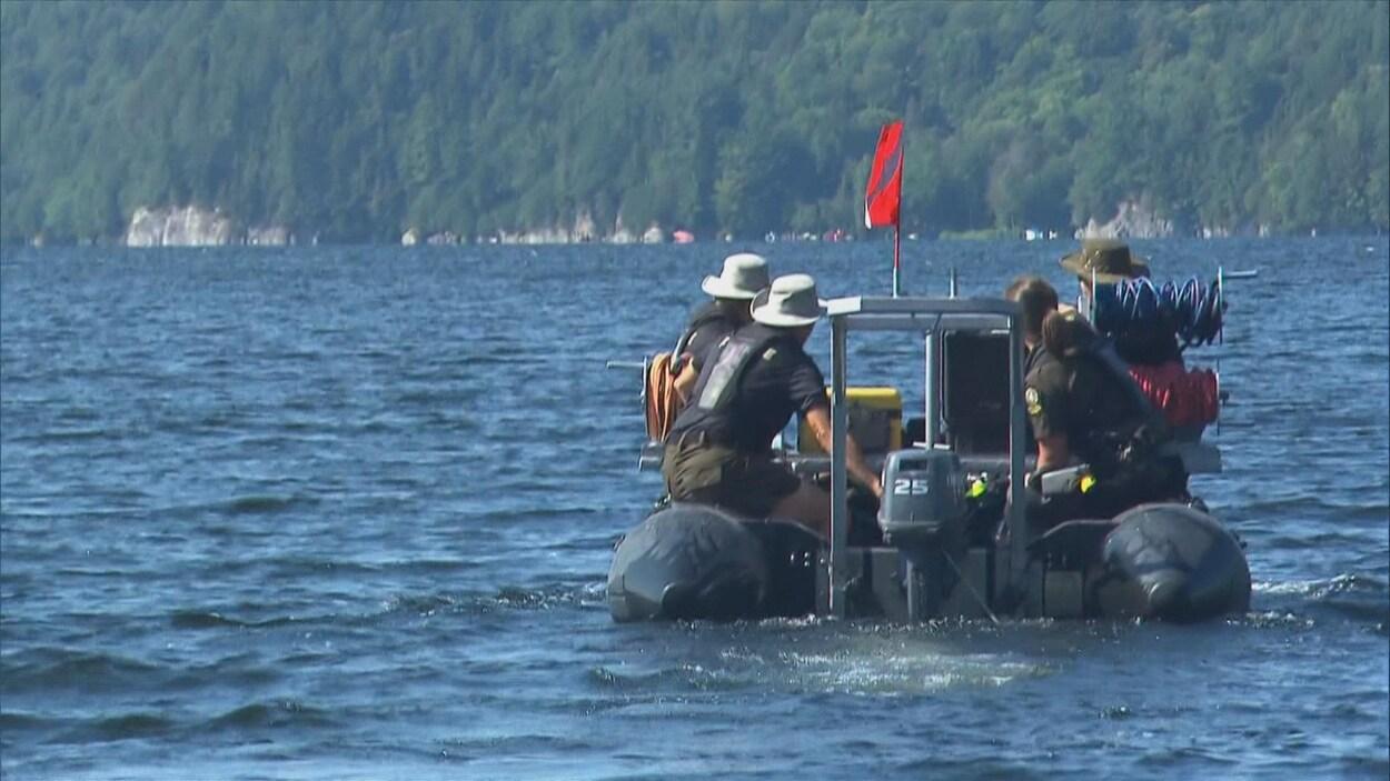 Des plongeurs de la SQ sont sur un zodiac pour tenter de retrouver le corps d'un jeu nageur porté disparu.