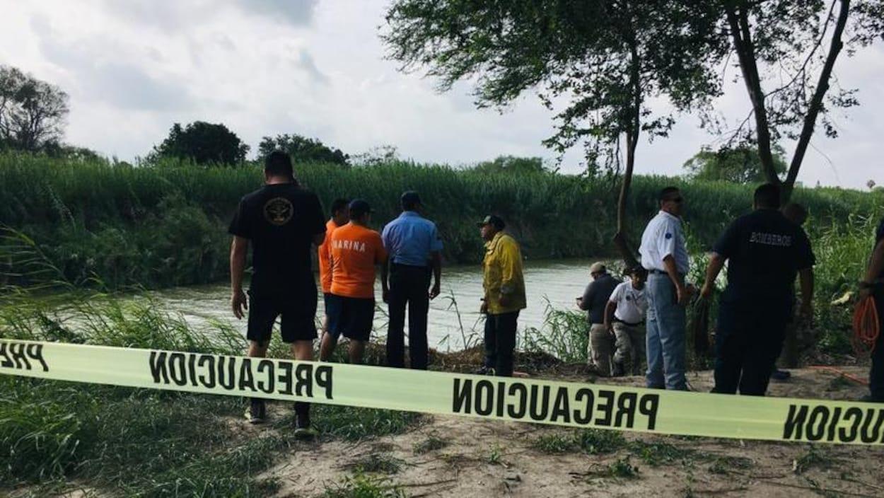 Plusieurs personnes des autorités se tiennent derrière un ruban jaune à proximité du Rio Grande, suite à la noyade d'un migrant salvadorien et de sa fille.