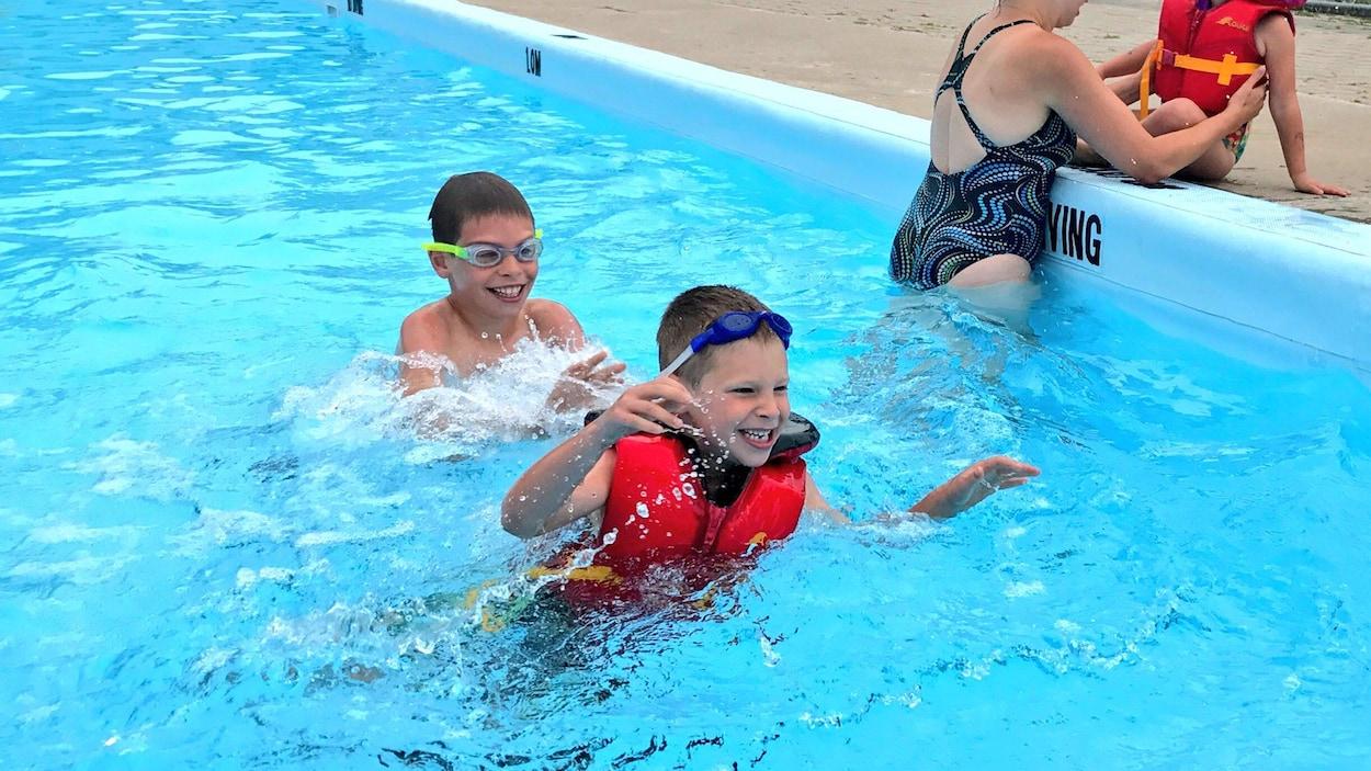 Des enfants jouent dans une piscine.