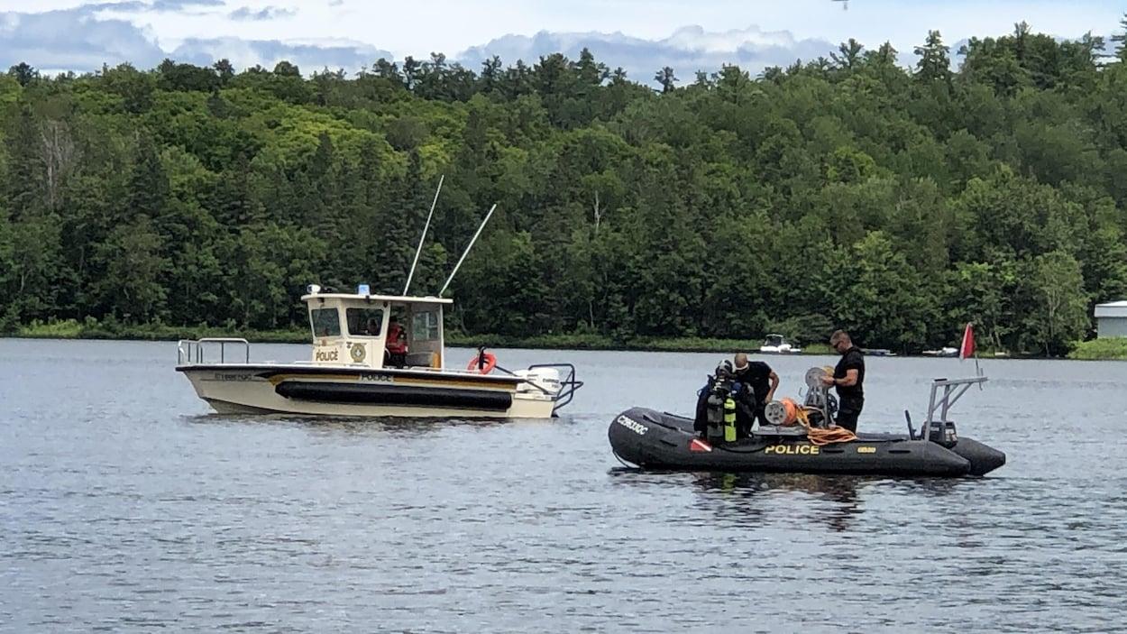 Des plongeurs de la Sûreté du Québec se déplacent dans deux bateaux sur le lac.