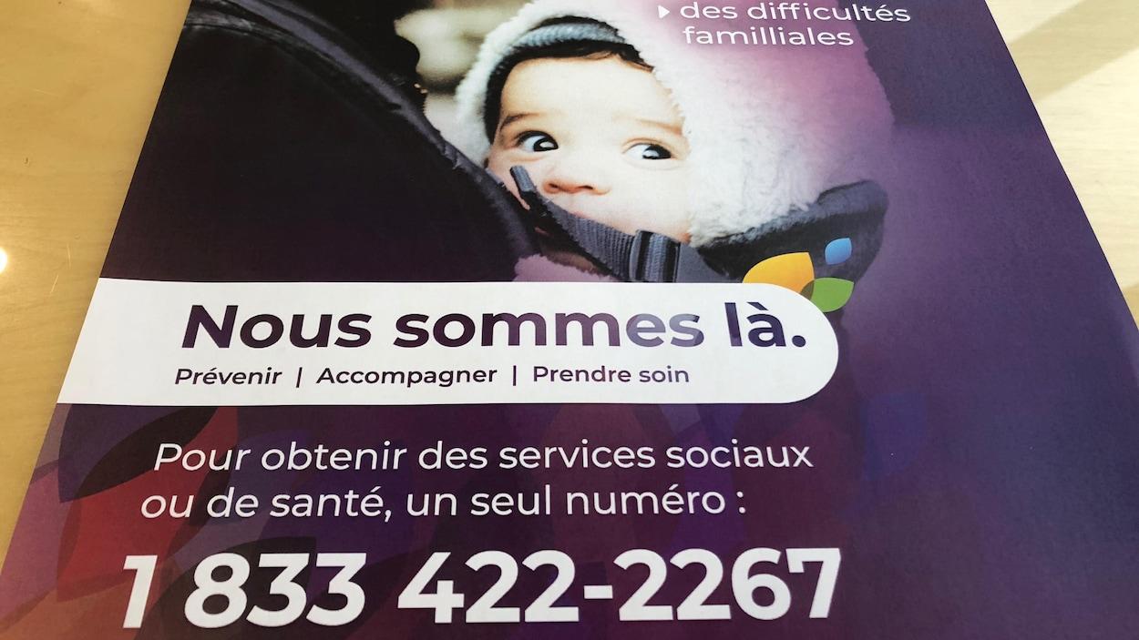 """Une affiche promotionnelle de la campagne """"Nous sommes là"""", qui indique un numéro de téléphone"""
