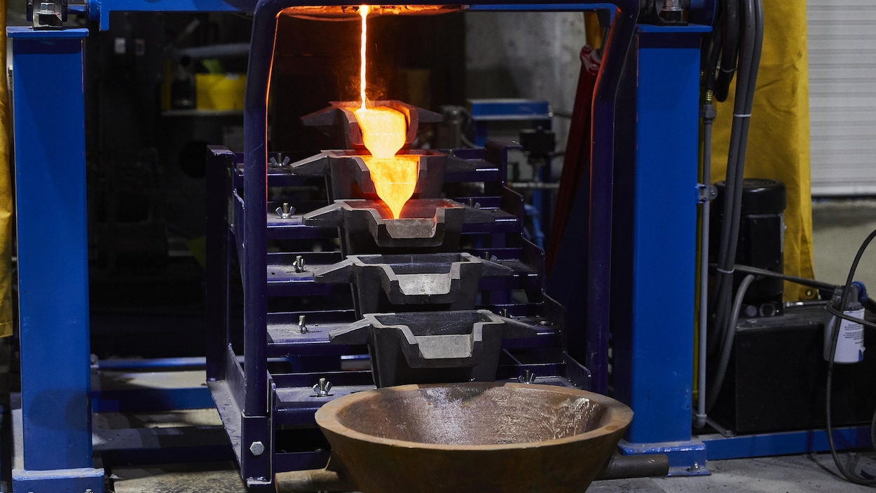 Une coulée de métal en fusion descend vers un réceptacle.