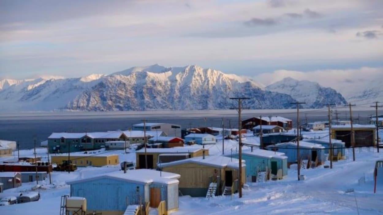 Un village enneigé devant une étendue d'eau et des montagnes.