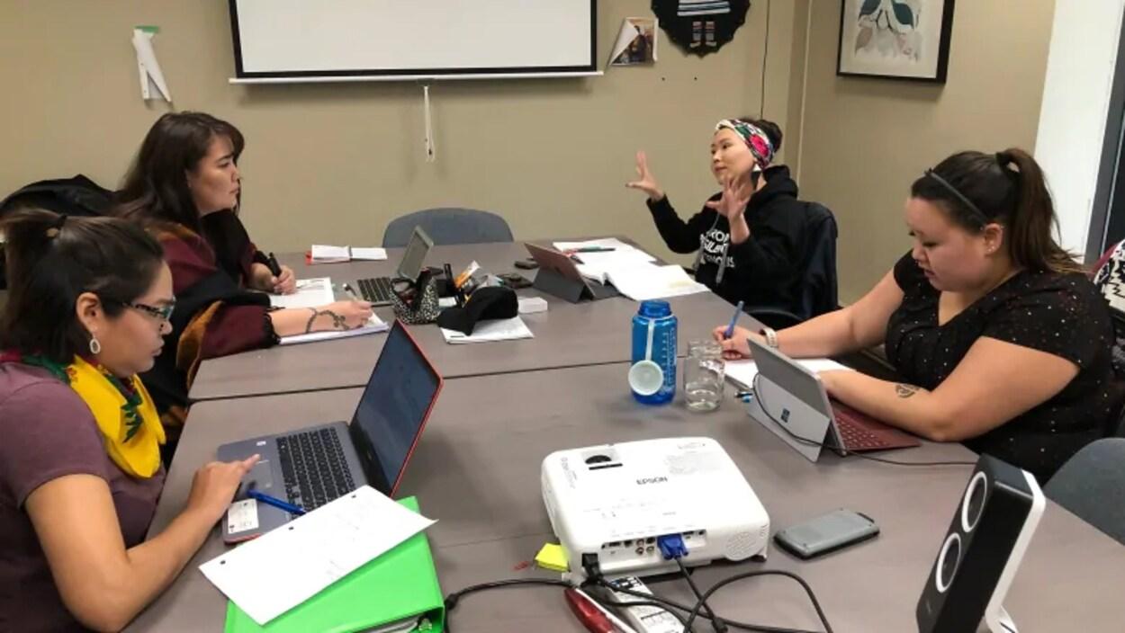 Quatre étudiantes discutent autour d'une table.