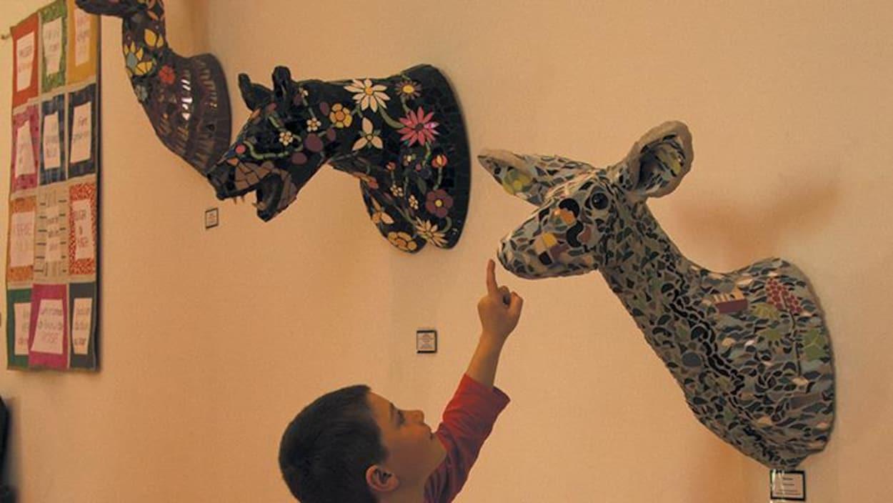 Un garçon avec un doigt près d'une sculpture représentant un cerf.