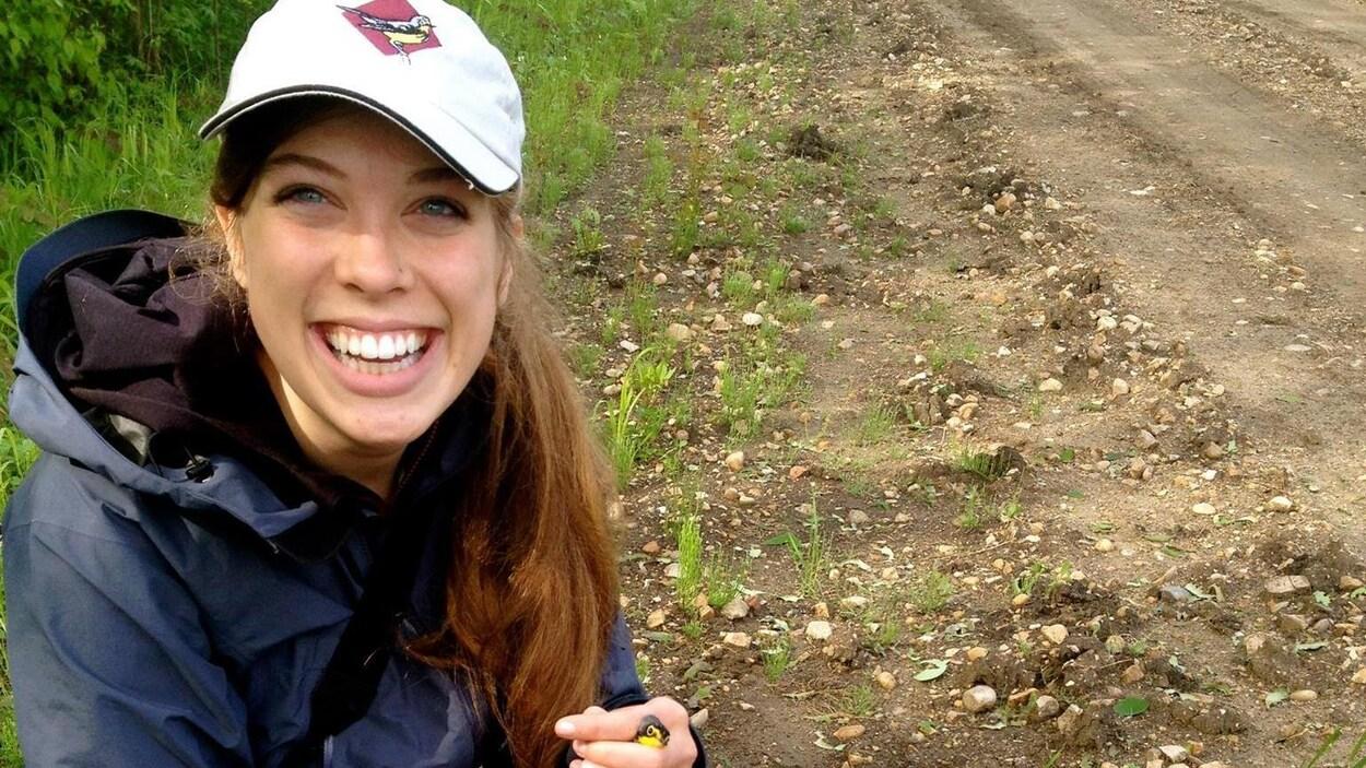 Une femme souriante portant une casquette avec une image d'oiseau est accroupie avec un minuscule oiseau jaune entre les mains.