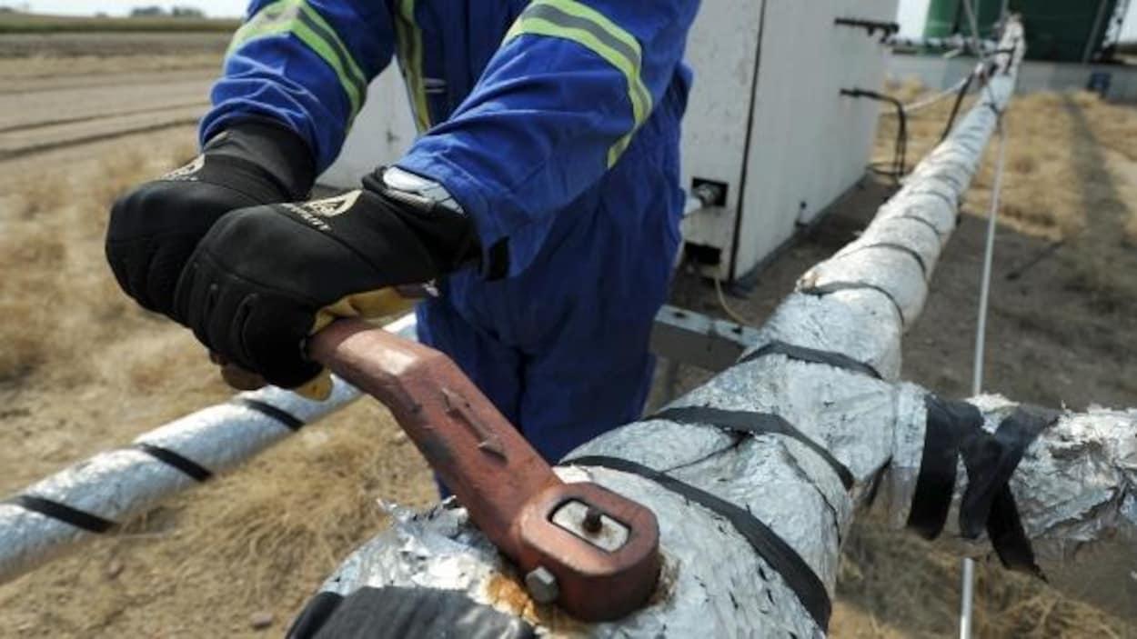 Un homme travaille sur un oléoduc.