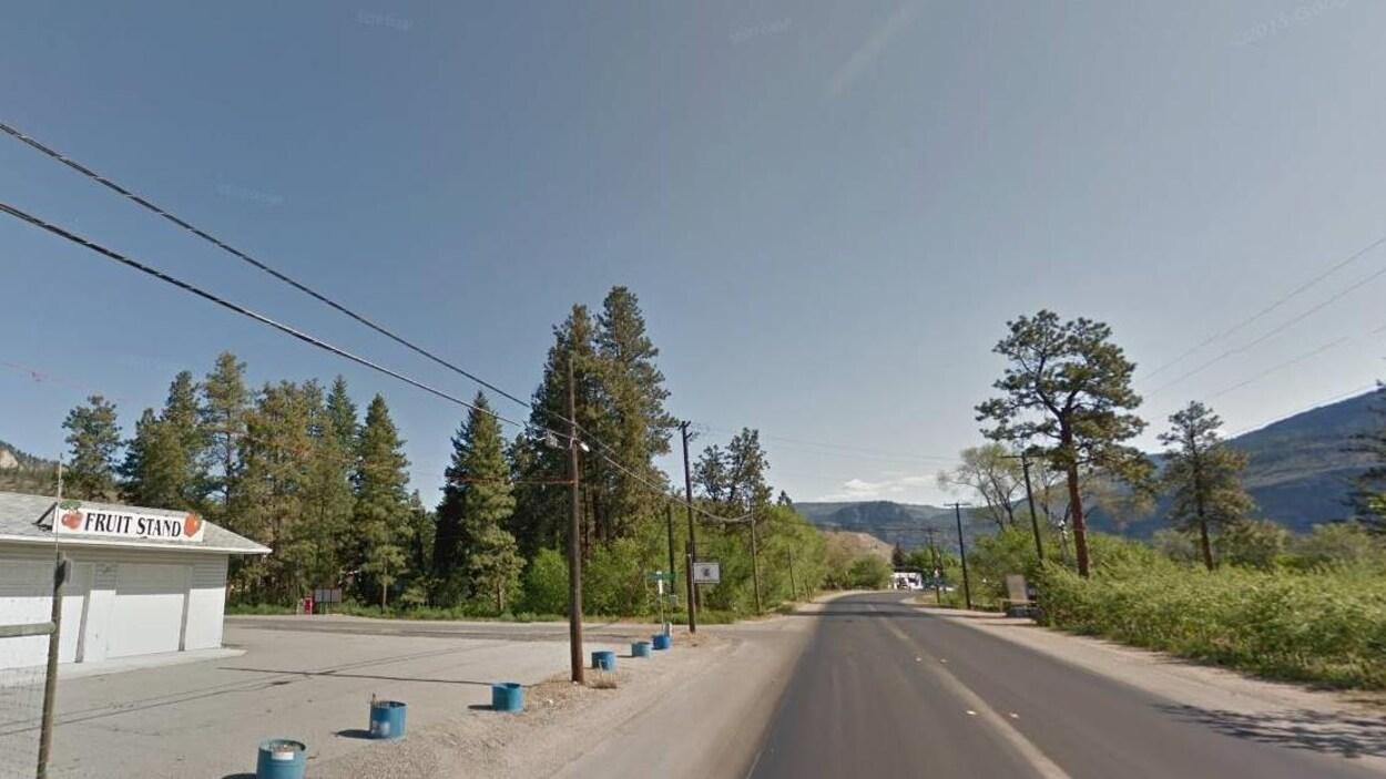 Une route à deux voies avec des arbres sur les côtés et un commerce de vente de fruits.