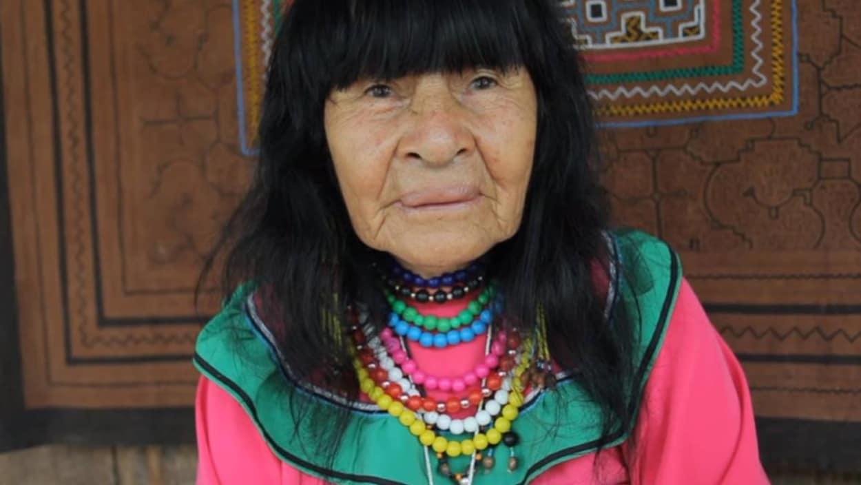 Une femme âgée habillée de couleur vive est debout devant un tissu avec des motifs autochtones.
