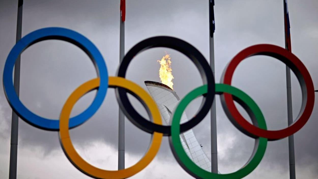 Les anneaux olympiques devant la flamme sous un ciel gris.