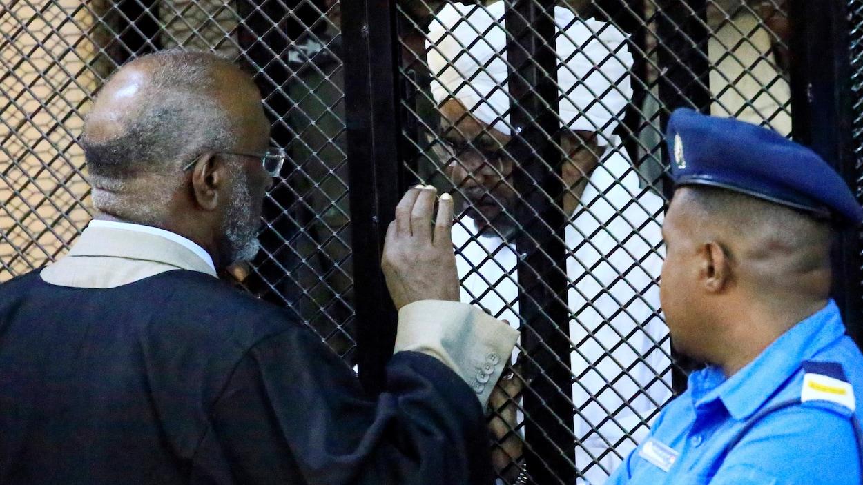 Omar El-Béchir est dans une cage grillagée.