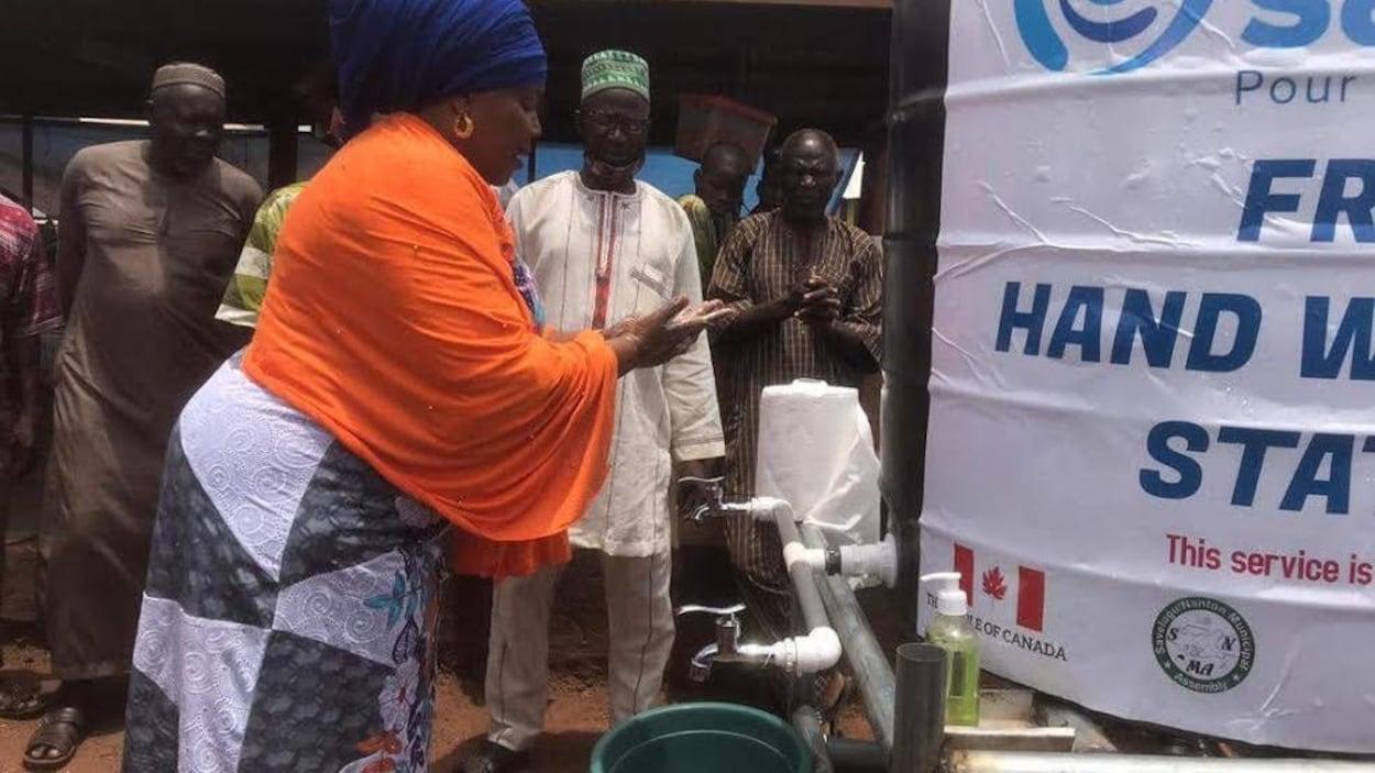 Une femme se lave les mains à une station de lavage durant la pandémie au Ghana.