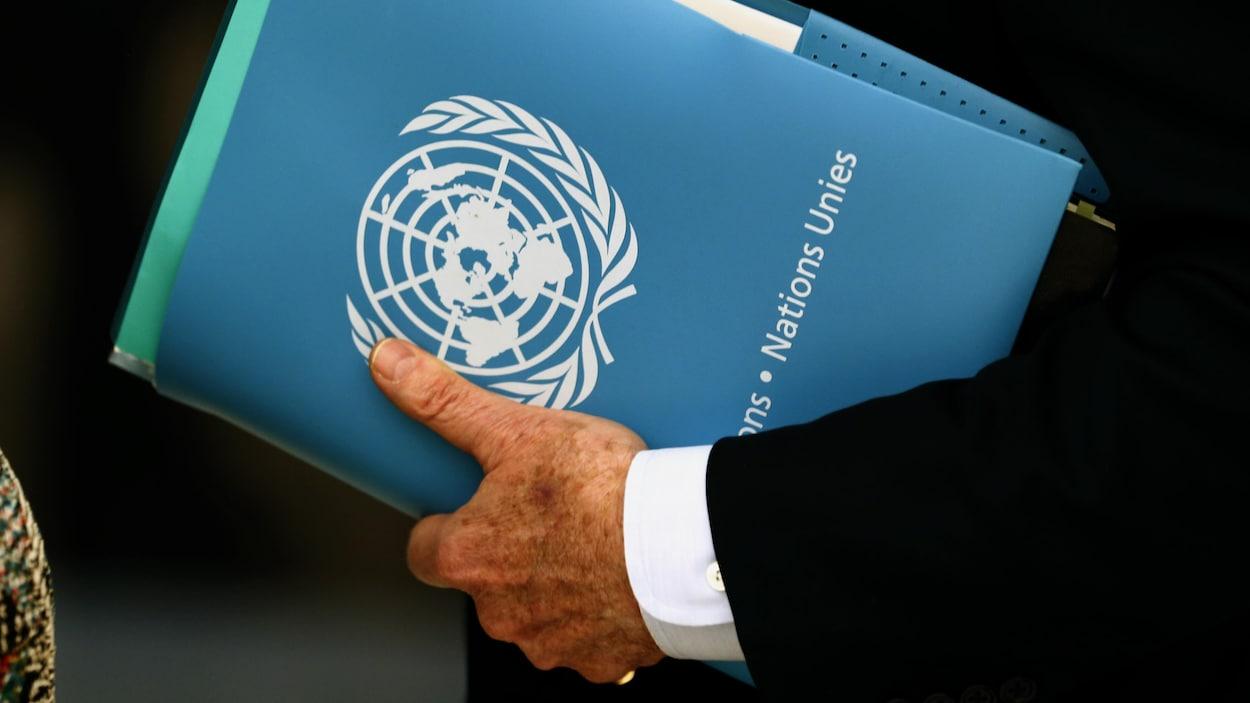 Un homme tient un classeur portant le logo de l'ONU.