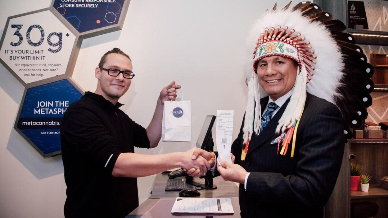 Un chef autochtone portant une coiffe autochtone et une veste sert la main d'un autre homme portant des lunettes et des lunettes noires.
