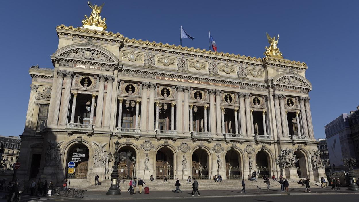Des gens sont assis sur les marches de l'Opéra Garnier, à Paris, en novembre 2015.