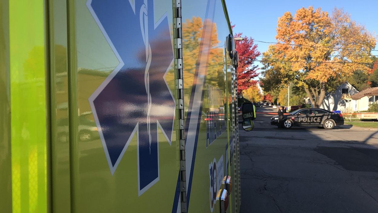 Une ambulance est stationnée dans la rue tandis qu'une autopatrouille est à proximité.