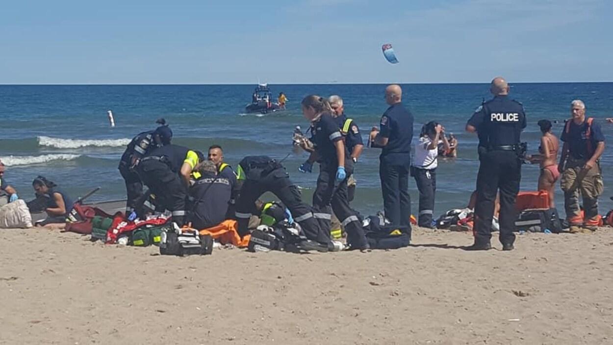 Plusieurs policiers et ambulanciers donnant les premiers soins.