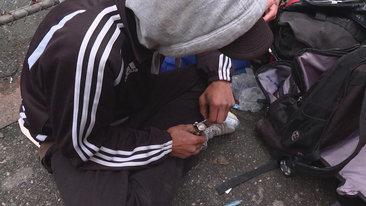 Un homme dont le visage est caché par une casquette se prépare une consommation de drogue. Il est assis par terre.