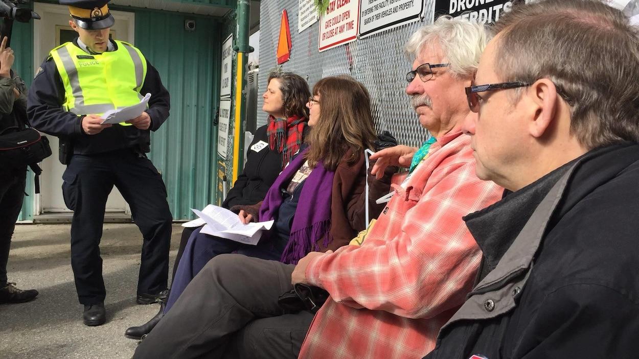 Un agent de la GRC de Burnaby en train de lire l'injonction à des manifestants qui se sont attachés à l'entrée du terminal pétrolier de Kinder Morgan.