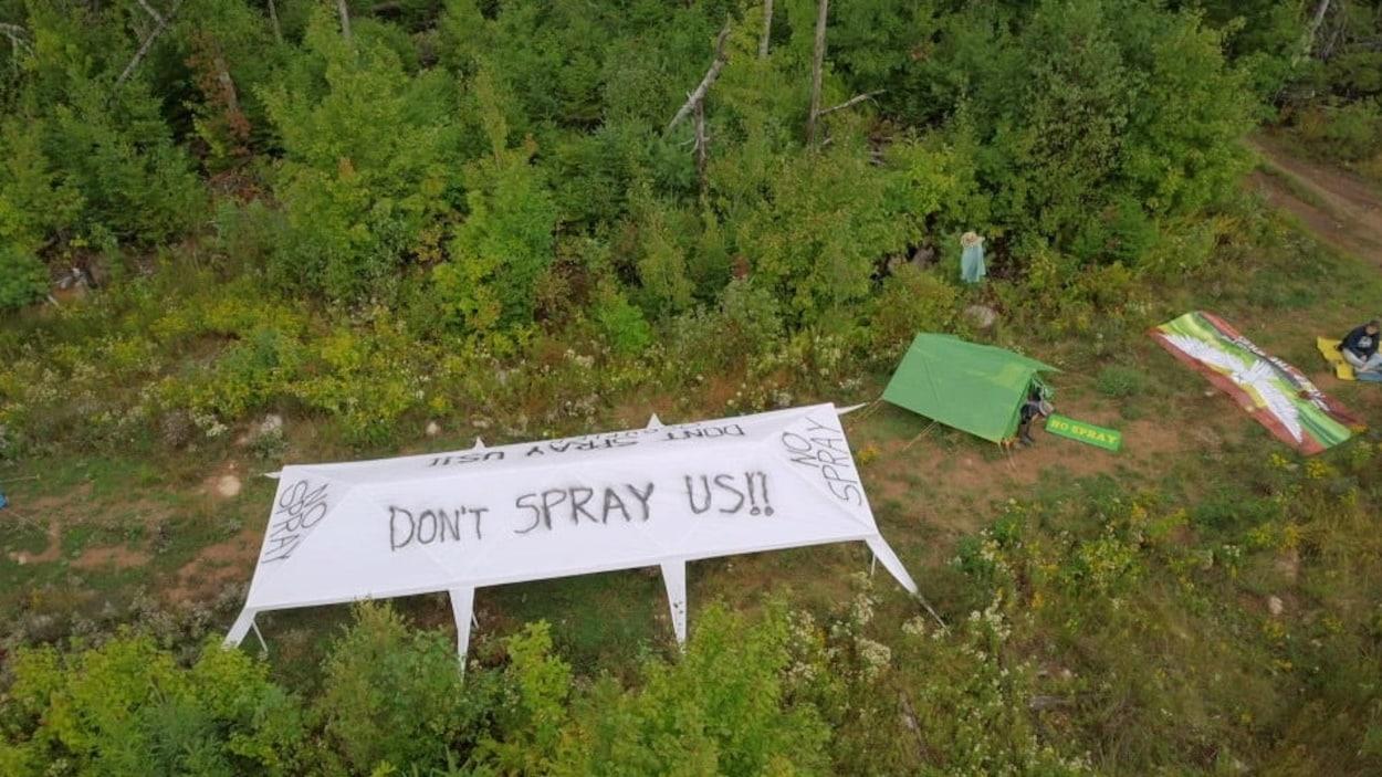Une grande tente en forêt sur laquelle il est écrit «Ne nous aspergez pas».