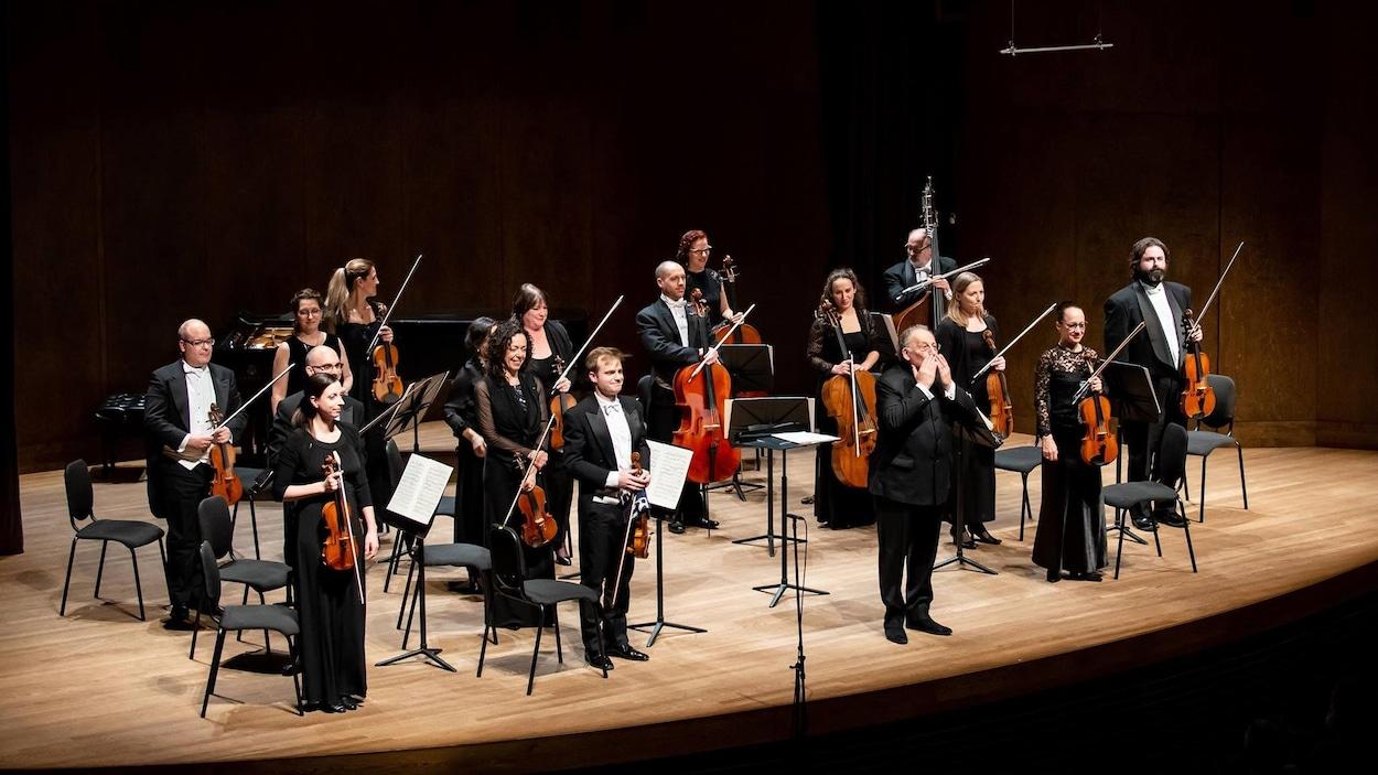 L'orchestre debout sur scène.