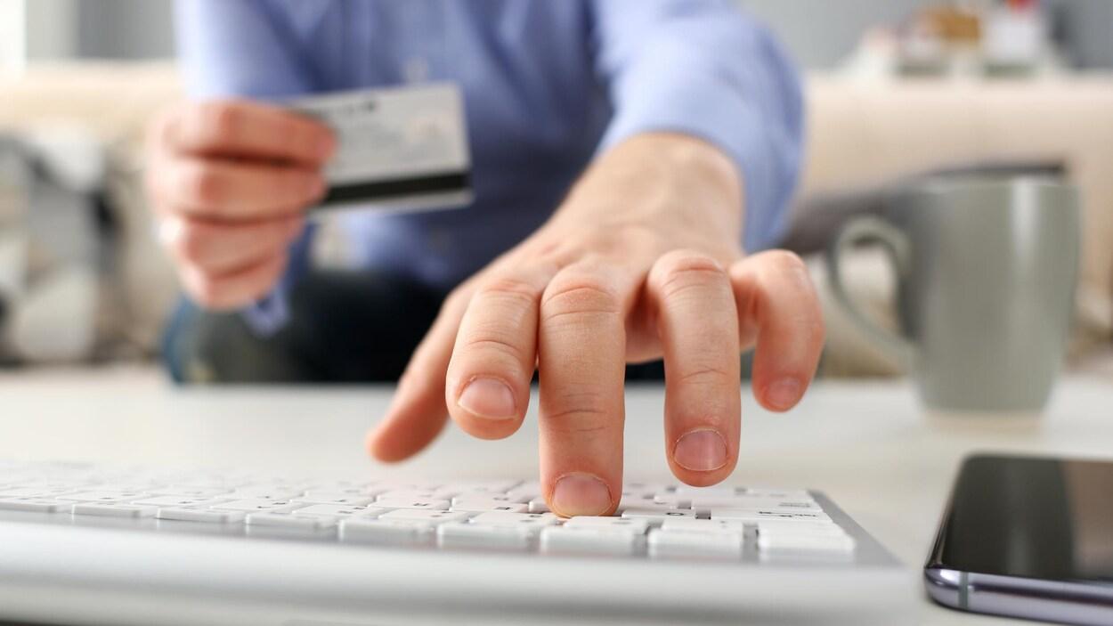 Une personne tient une carte de crédit en tapant sur son clavier.