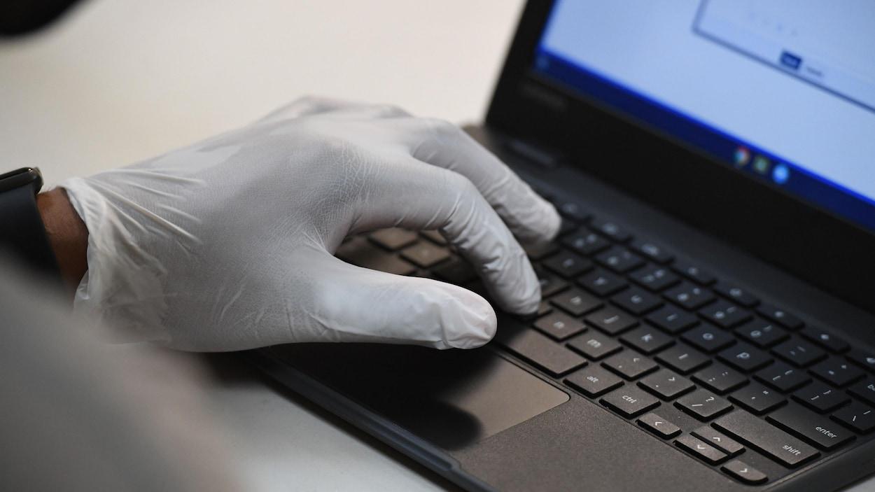 Une personne portant des gants de plastique utilise un ordinateur portable.