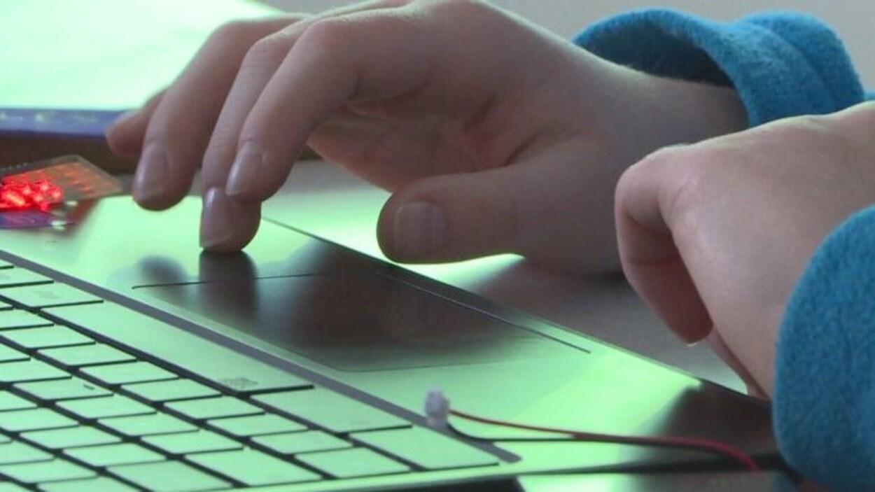 Les mains d'un élève en train de taper sur le clavier d'un ordinateur portable.