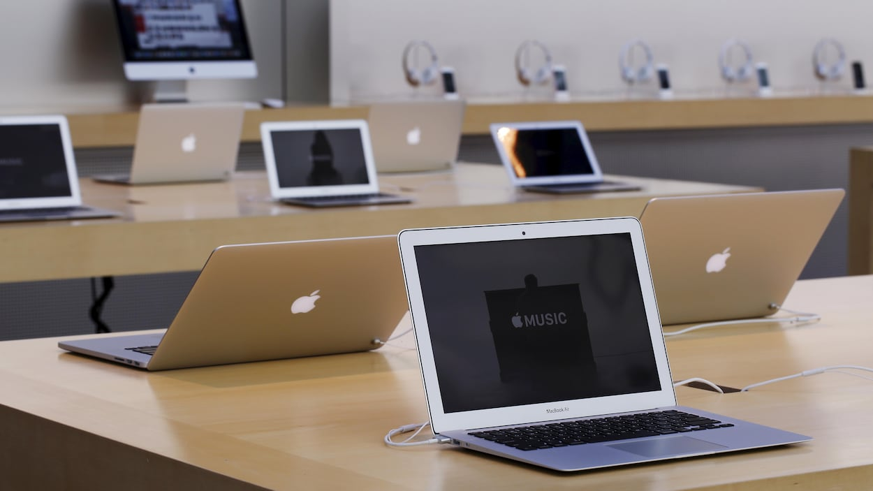 Plusieurs ordinateurs portables de la marque Apple sont ouverts sur des tables.