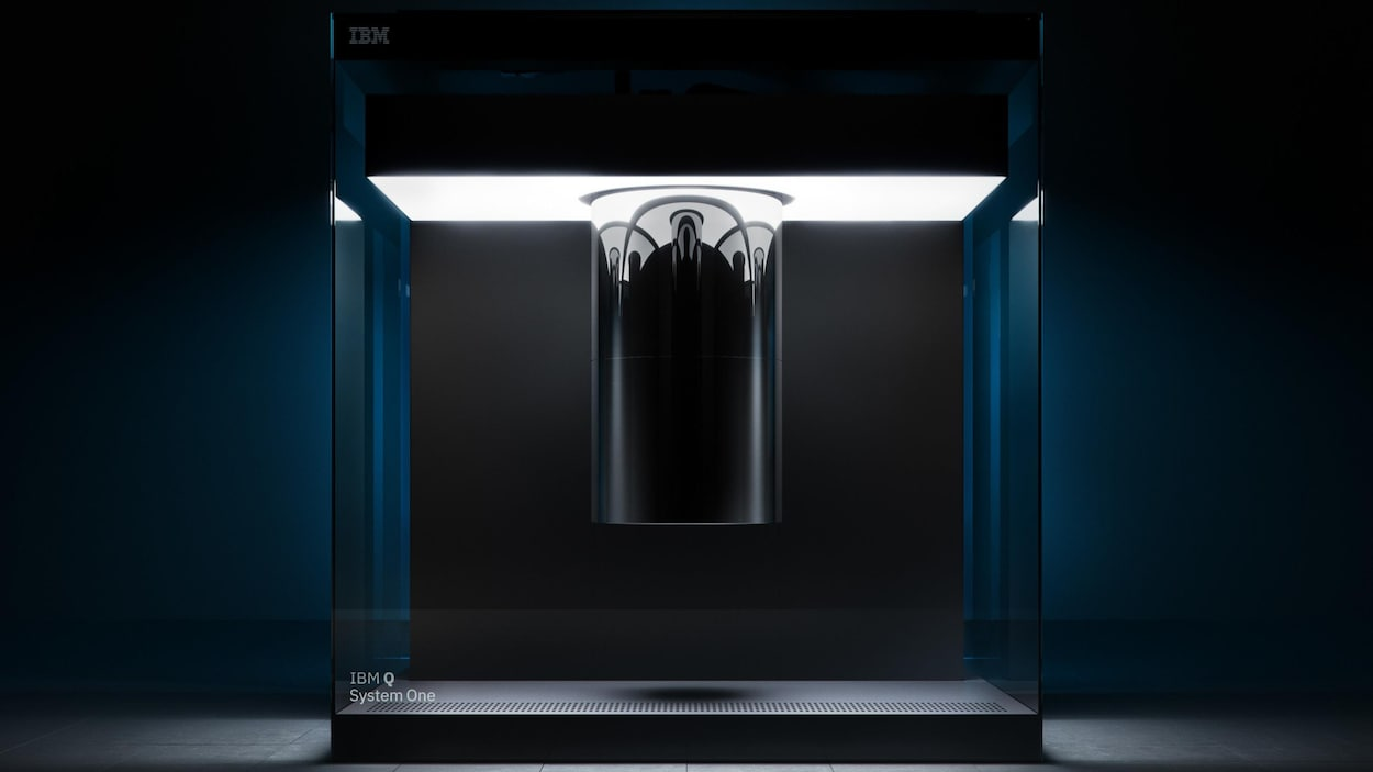 Une photo montrant l'ordinateur quantique Q System One d'IBM, un grand cube de verre contenant un cylindre chromé suspendu.