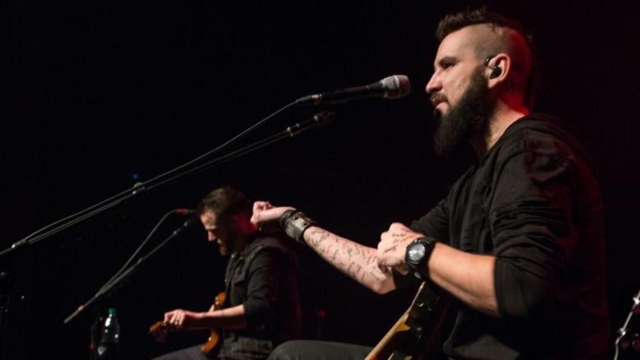Un musicien présente son bras recouvert de prénoms tatoués.