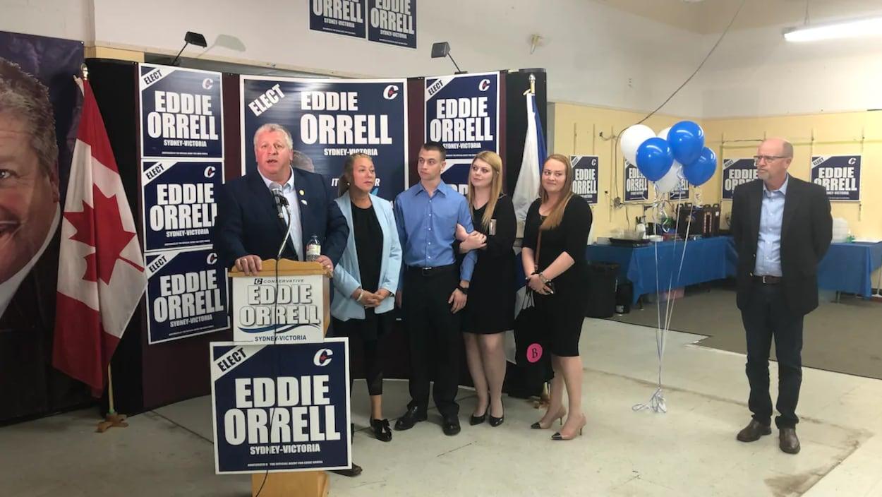 Cinq personnes aux côtés du candidat qui prononce un discours dans une salle communautaire
