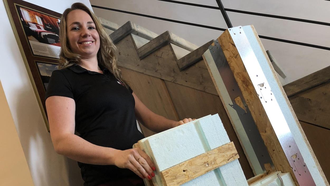 Une femme tient des matériaux de construction.